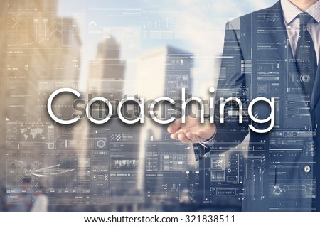 Businessman showing text by his hand: Coaching - stock photo