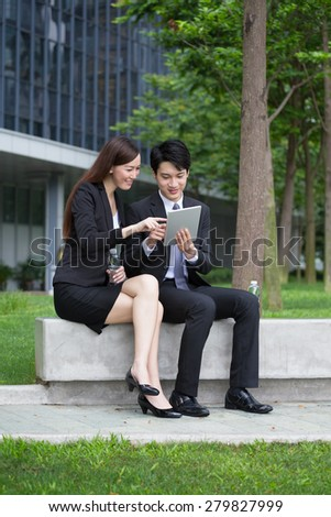 Businessman showing the detail on the digital tablet with secratary - stock photo