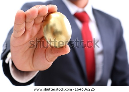 businessman showing the golden egg - stock photo