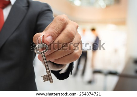 businessman showing the silver key to success - stock photo
