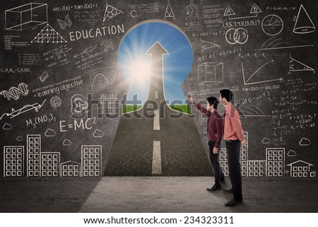 Businessman showing the way to success to another businessman - stock photo