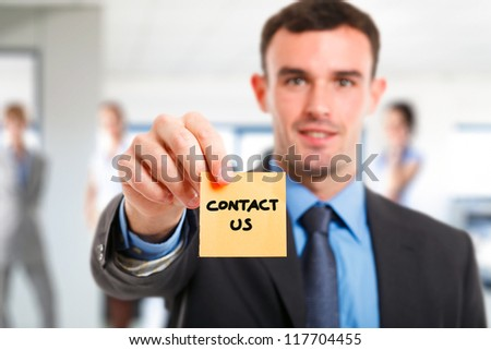 Businessman showing the words contact us on a post-it