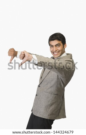 Businessman showing thumbs down and smiling - stock photo