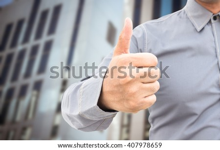 businessman showing thumbs up sign standing in office - stock photo