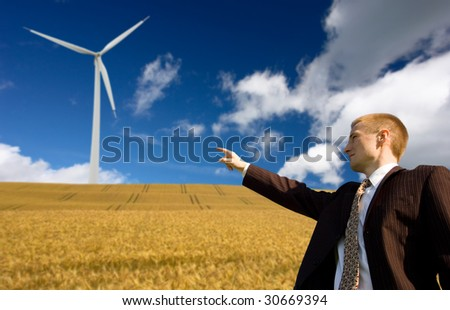 Businessman showing to the future green energy - wind energy conception - stock photo