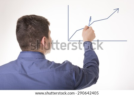 Businessman shows business growth on a graph - stock photo