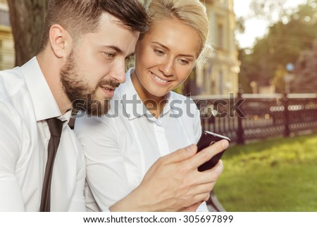 Businessman shows on your mobile phone information - stock photo