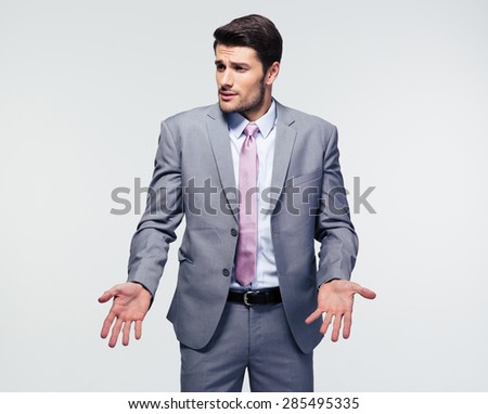 Businessman shrugging shoulders over gray background. Looking at camera - stock photo