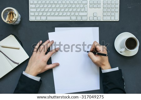 Businessman signature documents at office working table with notepad, computer and cup of coffee. Top view. - stock photo