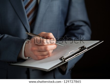Businessman signing a contract, black background - stock photo