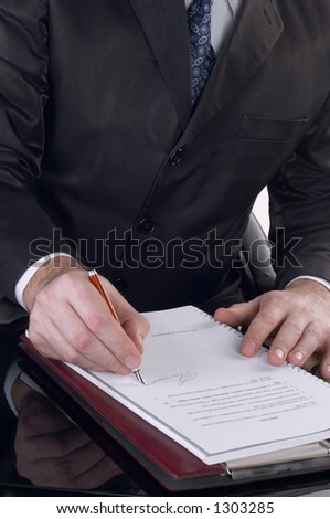 Businessman signing a document and working at his desk.