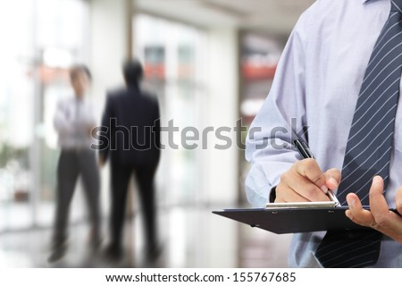 Businessman signing a document in the office  - stock photo