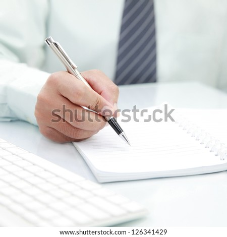 Businessman signing a document on the desk