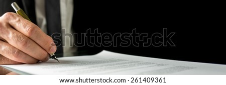Businessman signing a document or contract in the office, close up horizontal banner format of his hand and the paperwork with copyspace. - stock photo