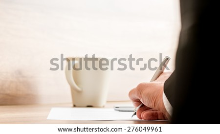 Businessman signing a document or contract with a mug of coffee standing on the desk, low angle view between his arm of the paperwork. - stock photo