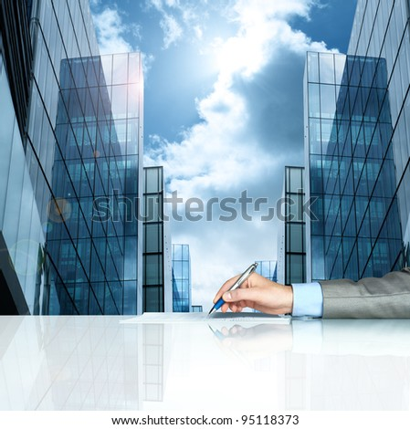Businessman signing contract against modern offices - stock photo