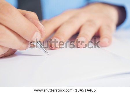 Businessman signing contract agreement, close up image with focus on hand holding a pencil and writing on a piece of paper.