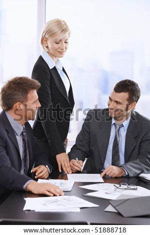 Businessman signing contract at meeting, smiling assistant pointing at document. - stock photo