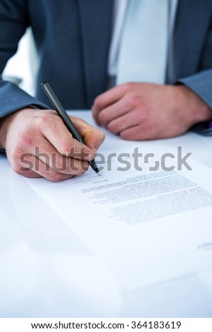 Businessman signing contract in a office