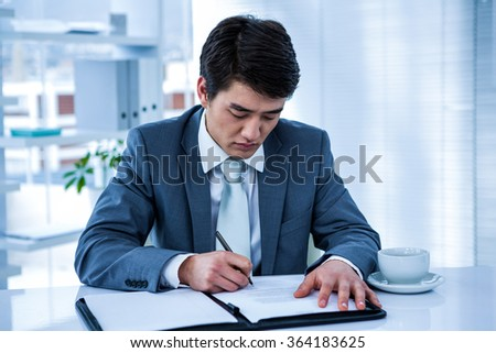 Businessman signing contract in his office - stock photo