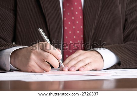 Businessman signing documents, focus on the pen.