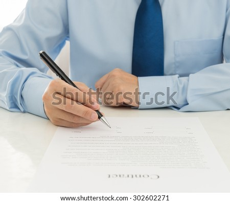Businessman signing the contract at office - stock photo