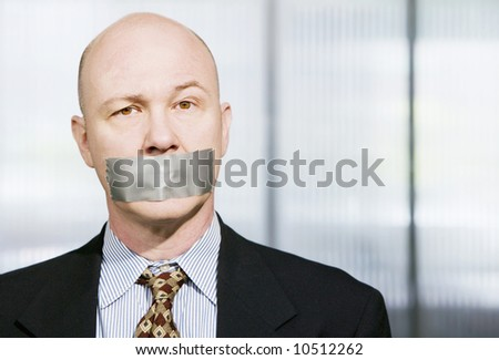 Businessman silenced with duct tape over his mouth - stock photo