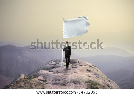 Businessman sinking a flag on the top of a mountain - stock photo