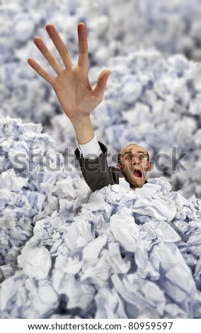Businessman sinking in big heap of crumpled papers and asking for help - stock photo