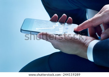 businessman sit touch screen mobile phone graph and statistics rising on screen   - stock photo