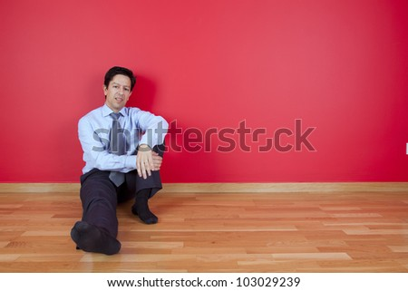 businessman sited in the floor of his new house - stock photo