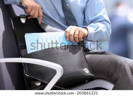 Businessman siting on a chair and getting out   documents with graphs  from his   leather briefcase.  - stock photo
