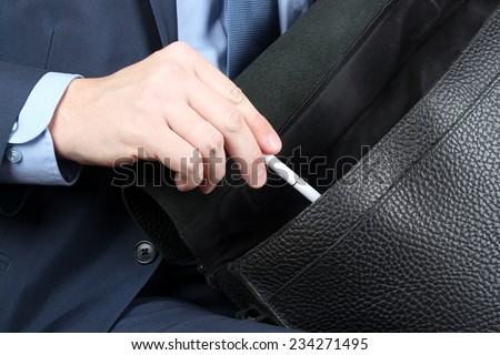 Businessman siting on a chair and putting down   a pen to  his   leather briefcase.  - stock photo