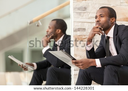 Businessman sits and thinks with his chin on his hand - stock photo
