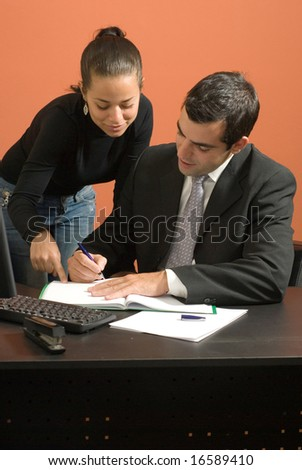 Businessman sits at desk working on paperwork with a businesswoman who stands by him. Vertically framed photo.