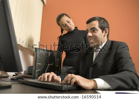 Businessman sits at his desk and looks at his computer while his co-worker stands up looking at him. Vertically framed photo.