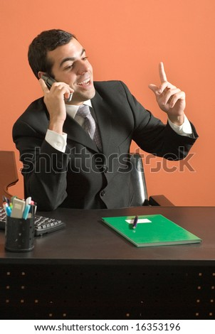 Businessman sits at his desk and speaks animatedly on his phone. Vertically framed photograph. - stock photo