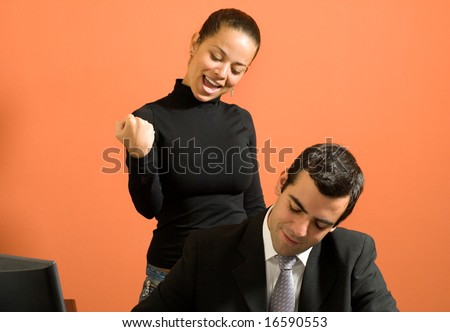 Businessman sits at his desk as his co-worker stands behind him and jokes around. Horizontally framed photo. - stock photo