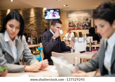 Businessman sitting alone in a cafe  with a coffee and reading the newspaper - stock photo