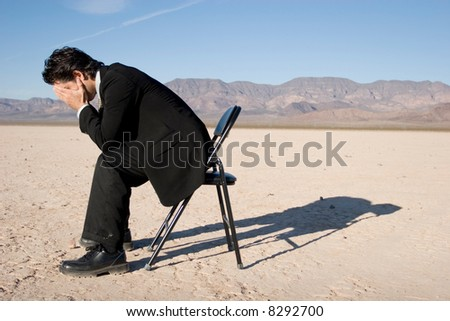 Businessman sitting alone in the empty desert - stock photo