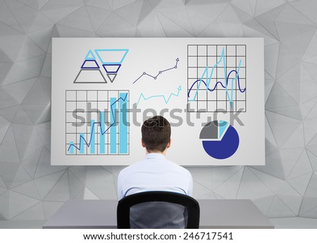 businessman sitting and looking to drawing graphs on placard - stock photo
