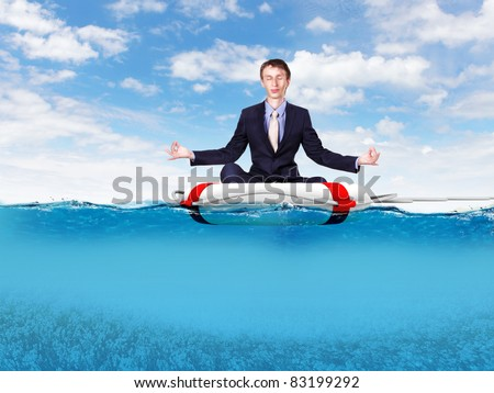 Businessman sitting and meditating on the rescue ring - stock photo