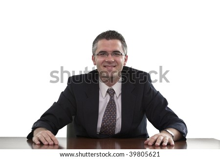 Businessman sitting and smiling with his hands on the table (white background) - stock photo