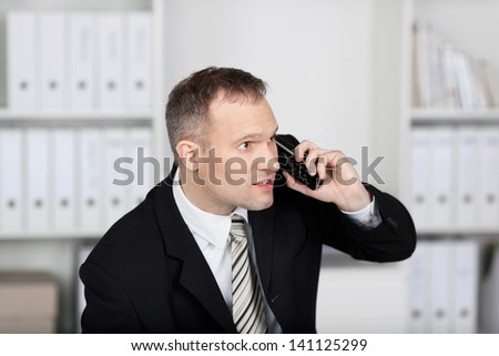 Businessman sitting and talking on the telephone at the office - stock photo