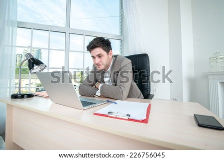Businessman sitting and working at a laptop. Young successful businessman with folded hands and looking at a laptop while sitting at a desk and a laptop in the office