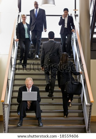 Businessman sitting and working on laptop on busy office stairs - stock photo