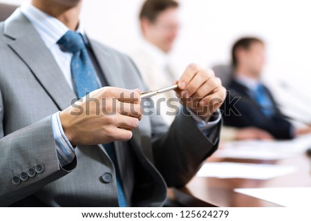 businessman sitting at a table and holding a pen - stock photo
