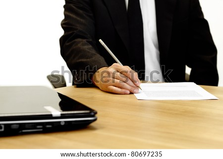 Businessman sitting at a table correcting a document with laptop