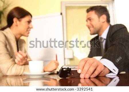 Businessman sitting at a table puts an electronic device aside to concentrate on work being discussed with a female colleague. - stock photo