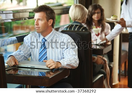 Businessman sitting at coffe table in cafe, waiter serving sweets to young women in the background. - stock photo